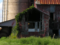Rustic old red barn with grey weathered barboard and concrete silo